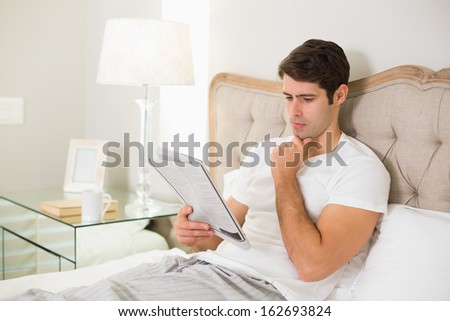 Casual young man reading newspaper in bed at home