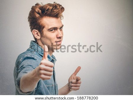 casual young man showing thumb up and smiling - stock photo