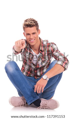 casual young man sitting cross legged and pointing and looking at the camera with a smile on his face