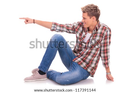 casual young man sitting / laying on the floor, looking and pointing to his side with a smile on his face. isolated on white - stock photo