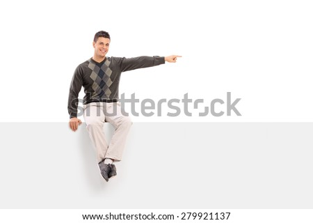 Casual young man sitting on a blank signboard, pointing with his hand and looking at the camera isolated on white background