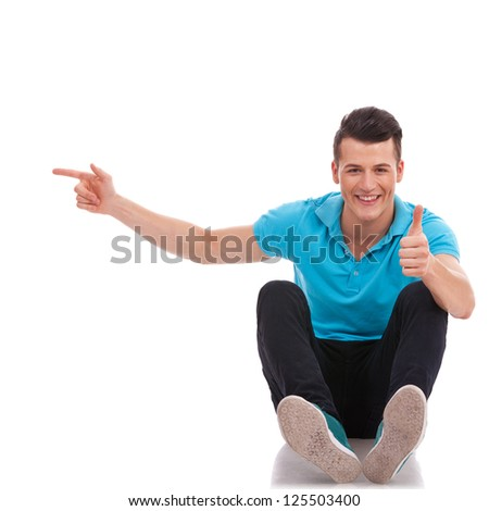 casual young man sitting on the floor and pointing to his side while looking at the camera and showing thumbs up sign. isolated on white - stock photo
