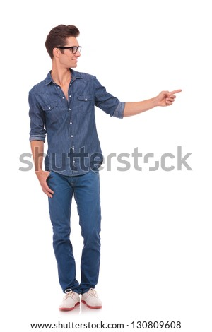 casual young man standing with a thumb in his pocket and pointing and looking to his side with a smile on his face. isolated on a white background - stock photo