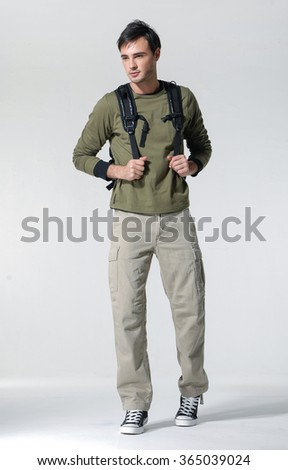 Casual young man standing with bag walking in studio - stock photo