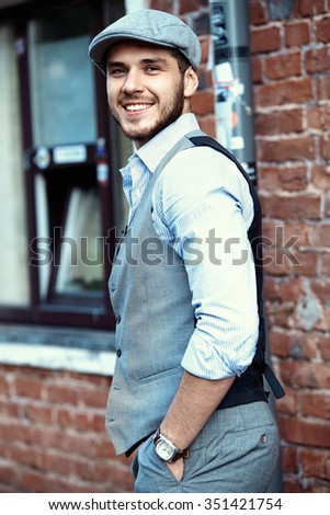 casual young man stands with his back against brick wall - stock photo