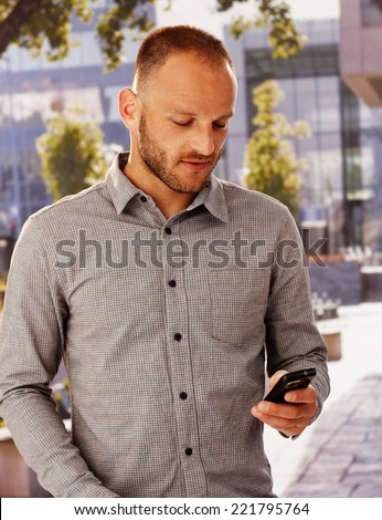 Casual young man using mobilephone outdoors, texting or dialing. - stock photo