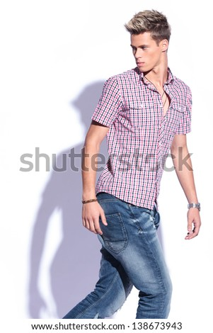 casual young man walking and looking back, away from the camera . on white background with shadow