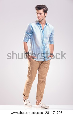 Casual young man walking on grey studio background with his hands in pockets, looking away from the camera. - stock photo