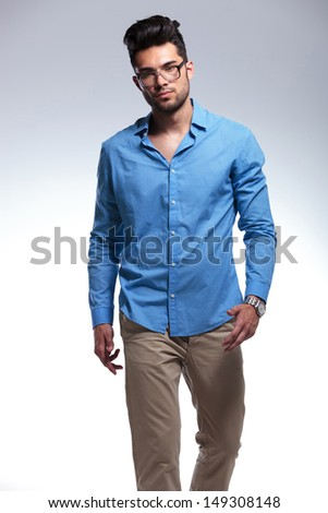 casual young man walking towards the camera. on light gray studio background