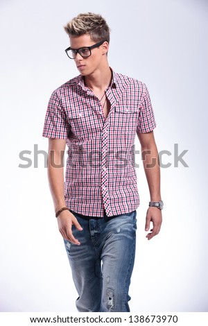 casual young man walking towards the camera while looking away from the camera. on gray background