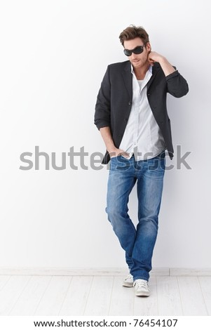 Casual young man wearing sunglasses, standing over white background. - stock photo