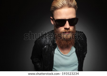 casual young man with a long beard looking up, into the camera. on a dark studio background