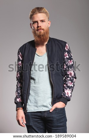 casual young man with a long red beard holding a hand in his pocket and looking into the camera. on gray studio background