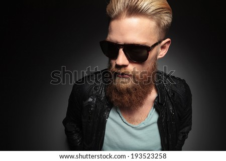 casual young man with an unshaved beard looks away while holding his hands at his back. on a dark studio background