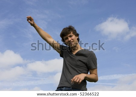 Casual Young man with his arm up on a blue sky - stock photo
