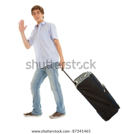 casual young man with suitcase waving hello, full length, white background - stock photo