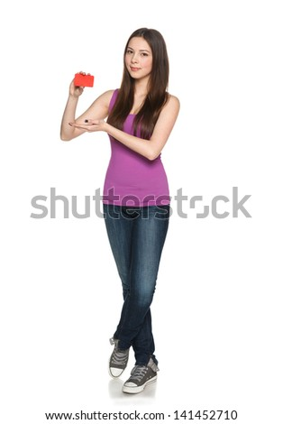 Casual young teen female showing blank credit card, in full length against white background - stock photo
