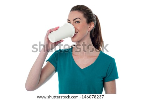 Casual young woman enjoying beverage