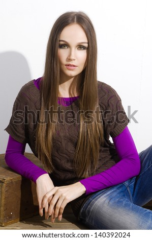 Casual young woman girl sitting on cube