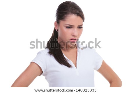 casual young woman looking down perplexed with her hands on her hips. isolated on white background