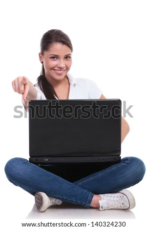 casual young woman sitting with legs crossed and pointing at the camera while holding her laptop. isolated on white background