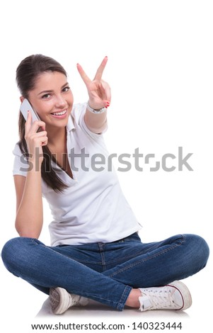casual young woman sitting with legs crossed and speaking on the phone while showing the victory sign. isolated on white background - stock photo