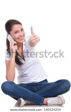 casual young woman sitting with legs crossed and talking on the phone while showing thumb up gesture and smiling at the camera. isolated on white background - stock photo