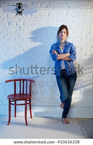 Casual young woman standing against wall arms crossed, looking down, thinking. - stock photo