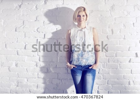 Casual young woman standing against white brick wall hands in pockets, smiling, looking at camera.