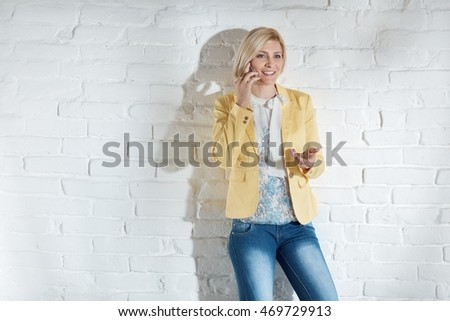 Casual young woman standing by white brick wall, talking on mobilephone, gesturing, smiling.