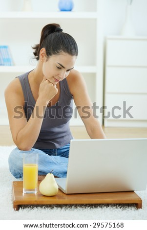 Casual young woman using laptop computer, sitting on floor in living room, leaning on hand and looking at screen.