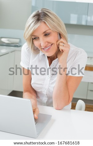 Casual young woman using laptop while on call in the kitchen at home