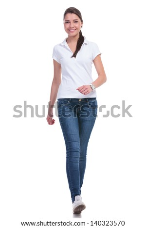 casual young woman walking to the camera with a smile. isolated on white background - stock photo