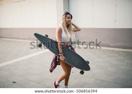 Casual young woman walking with her long board in the street
