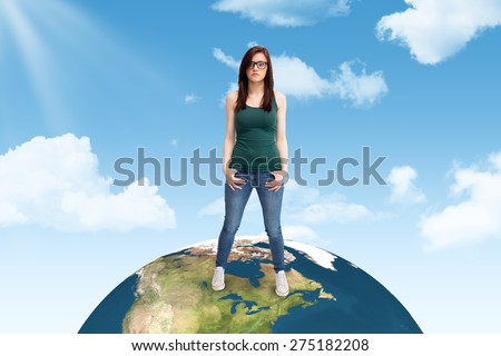 Casual young woman with glasses posing against blue sky - stock photo