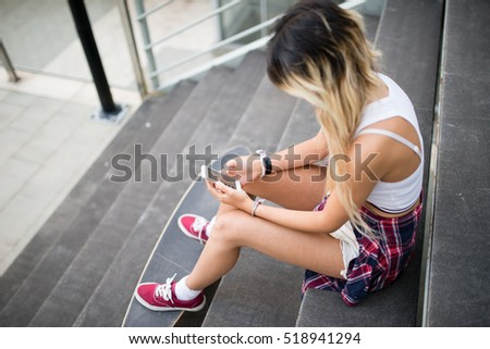 Casual young woman with her smart phone and long board in the street