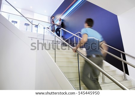 Casually dressed blurred businessman walking up stairs with colleagues in background - stock photo