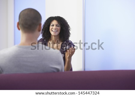 Casually dressed businesswoman talking to colleague in office - stock photo