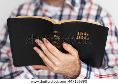 Casually Dressed Christian Guy Holding an Open Bible - stock photo