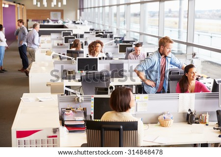 Casually dressed colleagues talking in an open plan office - stock photo
