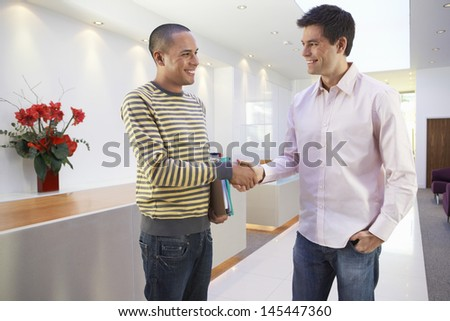 Casually dressed happy multiethnic businessmen shaking hands in office - stock photo