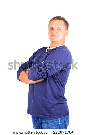 Casually dressed middle aged man with arms folded. 3/4 view of man shot in vertical format isolated on white.
