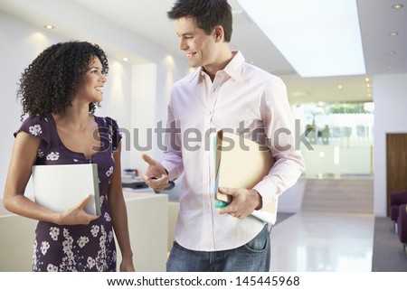 Casually dressed multiethnic office workers discussing at reception - stock photo