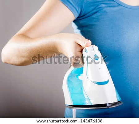 Casually dressed woman in blue shirt doing the ironing - stock photo