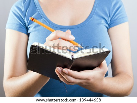 Casually dressed woman in blue shirt writing with a pencil in a small black notebook