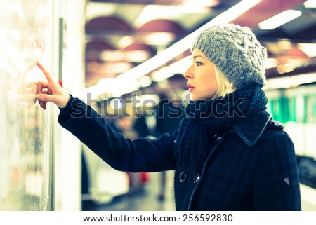 Casually dressed woman wearing winter coat, orientating herself with public transport map panel, pointing on her final destination. Urban transport. - stock photo