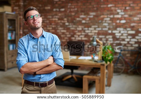 Casually dressed young businessman deep in thought while standing with his arms crossed in a brick walled office