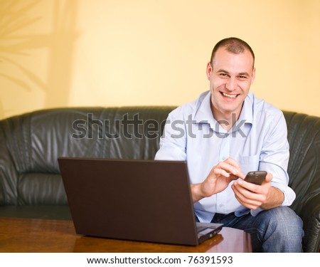 Casually dressed young businessman using mobile phone and laptop. - stock photo