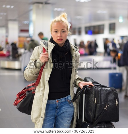 Casually dressed young female traveller walking in airport terminal hall with collected laggage after flight arrival . Blured background. Can also be used as railway, metro, bus station.