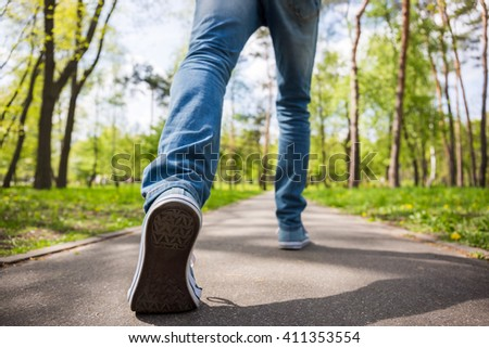 Casually dressed young man making a big step, low perspective - stock photo